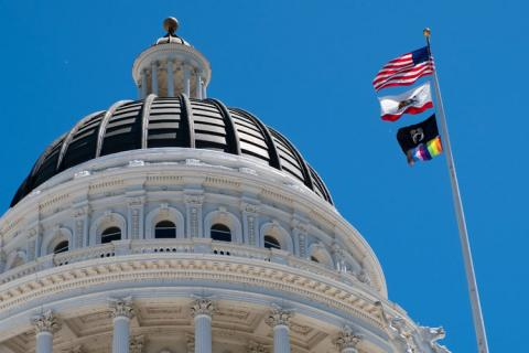 California State Capitol with flag pole containing American flag, California State flag, National League of Families POW/MIA flag, Progress LGBTQ Pride flag